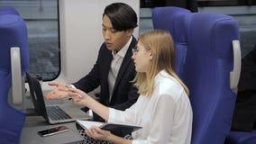 Giovani impiegati multietnici che lavorano e che parlano in treno all'interno video d archivio