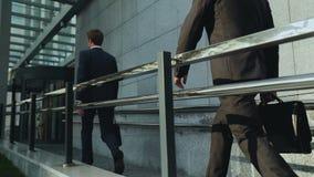 Giovani imprenditori che entrano nell'edificio per uffici, gente di affari, arrivisti stock footage