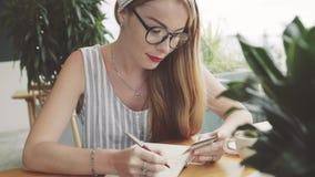 Giovani informazioni graziose di scrittura della donna dalla carta al taccuino Fotografia Stock