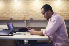 Giovani insegnante e studente mentre lavorando nell'ufficio moderno facendo uso delle tecnologie e del wifi Fotografia Stock Libera da Diritti