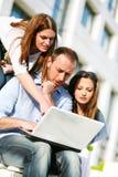 Giovani istituti universitari che lavorano al computer portatile Fotografia Stock