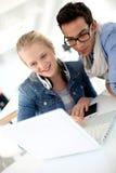 Giovani in istituto universitario facendo uso del computer portatile Immagine Stock Libera da Diritti