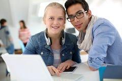 Giovani in istituto universitario facendo uso del computer portatile Fotografia Stock