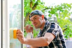 Giovani lavavetri con un detersivo dello spruzzo su vetro Immagine Stock