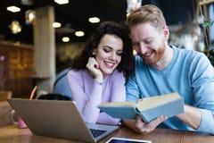 Giovani libri di lettura delle coppie in caffetteria Immagine Stock