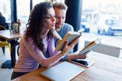 Giovani libri di lettura delle coppie in caffetteria Fotografie Stock