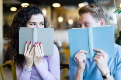 Giovani libri di lettura delle coppie in caffetteria Fotografia Stock