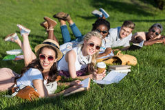 Giovani libri di lettura multietnici degli studenti mentre trovandosi sull'erba verde in parco Fotografie Stock