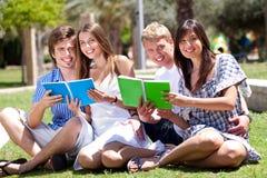 Giovani libri sorridenti della holding delle coppie Fotografia Stock