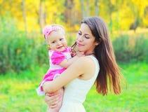 Giovani madre e bambino felici sulle mani di estate Immagine Stock