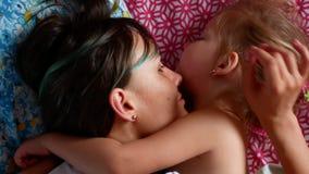 Giovani madre e figlia divertendosi nella camera da letto, clip del movimento lento 4k stock footage