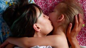 Giovani madre e figlia divertendosi nella camera da letto, clip del movimento lento 4k archivi video