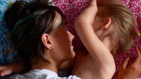 Giovani madre e figlia divertendosi nella camera da letto, clip del movimento lento 4k video d archivio
