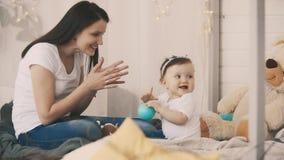 Giovani madre e figlia divertendosi nella camera da letto con il giocattolo al rallentatore archivi video