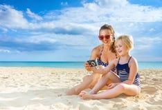 Giovani madre e figlia felici sulle foto di osservazione del litorale Fotografie Stock Libere da Diritti