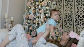 Giovani madre e figlia nella mattina del nuovo anno sul letto a casa video d archivio