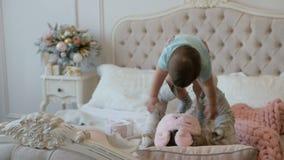 Giovani madre e figlia nella mattina del nuovo anno sul letto a casa archivi video