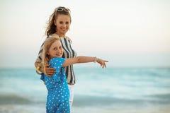 Giovani madre e figlia sorridenti che indicano a qualcosa fotografia stock libera da diritti