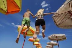 Giovani mani della holding delle coppie mentre saltando Fotografia Stock