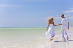 Giovani mani della holding delle coppie su una spiaggia tropicale Fotografie Stock Libere da Diritti