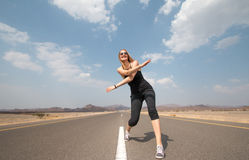 Giovani mani esili dell'incrocio della donna su una strada vuota Fotografia Stock Libera da Diritti