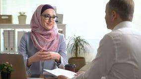 Giovani mani musulmane di scossa della donna di affari con un uomo caucasico nel corso di una riunione nell'ufficio stock footage
