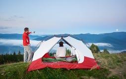 Giovani manifestazioni maschii turistiche via alla luna il suo compagno femminile in montagne all'alba fotografie stock