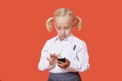 Giovani messaggi di testo della lettura della ragazza della scuola sopra fondo arancio Fotografia Stock