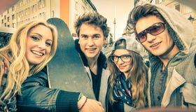 Giovani migliori amici dei pantaloni a vita bassa che prendono un selfie nel contesto urbano della città Fotografie Stock