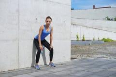 Giovani, misura e donna sportiva stanti davanti alla parete concreta del cemento Forma fisica, sport, pareggiare urbano e sano Fotografia Stock