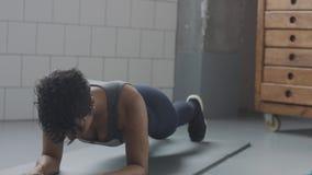 Giovani misura e tono sulla donna che fa allenamento di forma fisica con gli elementi della plancia per gli ABS di forza in sotto Fotografia Stock