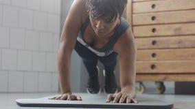 Giovani misura e tono sulla donna che fa allenamento di forma fisica con gli elementi della plancia per gli ABS di forza in sotto Immagini Stock