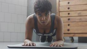Giovani misura e tono sulla donna che fa allenamento di forma fisica con gli elementi della plancia per gli ABS di forza in sotto Immagini Stock Libere da Diritti