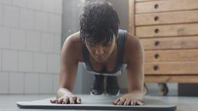 Giovani misura e tono sulla donna che fa allenamento di forma fisica con gli elementi della plancia per gli ABS di forza in sotto Fotografia Stock Libera da Diritti