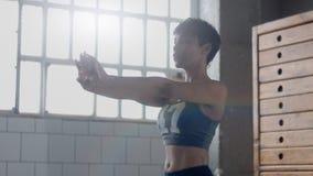 Giovani misura e tono sulla donna che fa riscaldamento prima di un allenamento di forma fisica in sottotetto soleggiato Immagine Stock