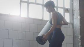 Giovani misura e tono sulla donna che prepara lo scorrevole di allenamento del tappeto per l'allenamento della plancia Fotografia Stock