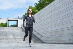 Giovani, misura ed alto corrente della donna sportiva le scale Forma fisica, sport, pareggiare urbano e concetto sano di stile di Immagine Stock
