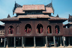 Giovani monaci alla finestra della chiesa di legno in tempio Immagine Stock