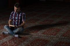 Giovani musulmani Guy Reading The Koran Fotografie Stock Libere da Diritti