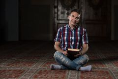 Giovani musulmani Guy Reading The Koran Immagine Stock Libera da Diritti