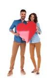 Giovani nelle coppie di amore che tengono grande cuore rosso Fotografia Stock