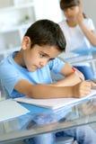 Giovani note di scrittura del ragazzo alla scuola Fotografia Stock Libera da Diritti