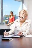 Giovani note di scrittura della donna di affari Immagine Stock
