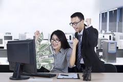 Giovani operai con soldi sul monitor Immagini Stock Libere da Diritti