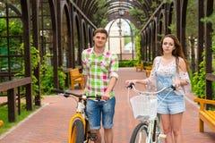 Giovani paia attraenti con le bici in arco Fotografia Stock Libera da Diritti