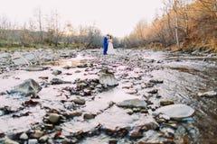 Giovani paia nuziali romantiche del vino bevente sulla sponda del fiume rocciosa del ciottolo con Forest Hills e la corrente Immagini Stock Libere da Diritti