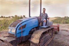 Giovani pani tostati dell'agricoltore su un trattore a cingoli Immagini Stock