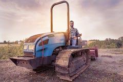 Giovani pani tostati dell'agricoltore su un trattore a cingoli Fotografie Stock Libere da Diritti