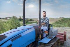 Giovani pani tostati dell'agricoltore su un trattore a cingoli Fotografia Stock Libera da Diritti