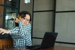 Giovani pantaloni a vita bassa asiatici stanchi che allungano duro dopo il lavoro con il computer portatile in ufficio Immagini Stock Libere da Diritti